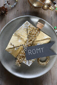 Christmas place setting with golden serviette, name tag and gold beads in test tube