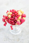 Raspberries, golden raspberries and redcurrants in a footed crystal bowl