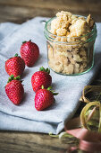 Strawberries and a jar of crumbles as ingredients for cake or dessert