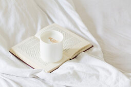 Cafe latte on a book on a bed