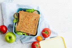 Gesundes Sandwich mit Gemüse, Schinken, Tomate und Käse in Lunchbox