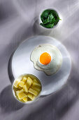 A fried egg served with salted potatoes and spinach