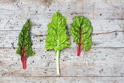 Three chard leaves on a wooden surface