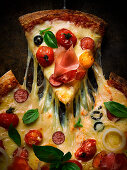 A pizza topped with salami, ham, tomatoes, olives and cheese