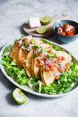 Tacos de papa (with potato filling) on salad with tomato salsa