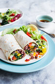 Vegan burrito with vegetables and wild rice, drizzled with oil chilli sauce