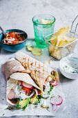 Two wraps filled with lentils, rucola, radish, avocado, tomaoes and onions