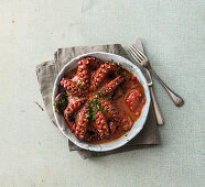 Braised octopus in tomato sauce with parsley and garlic pesto