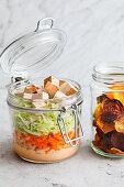 Coleslaw with vegetable crisps in jars