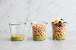 A salad being layered in a jar