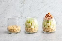 Muesli being layered in a jar
