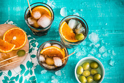 Three glasses of iced vermouth with green olives and orange slices on a turquoise surface