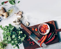 Still life with chili peppers, garlic, ginger and coriander leaves