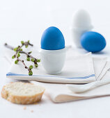 Blue dyed easter eggs in egg cups on a cloth napkin