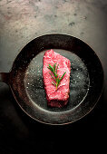 A beef steak with rosemary in a pan