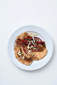 Chicken schnitzel in balsamic sauce with pistachios, ham strips and parmesan