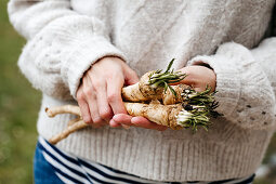 A woman holding freshly harvested, home-grown horseradish