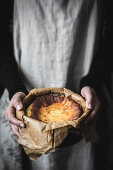 Hands holding cooking pot with cheese cake
