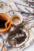 Filter coffee next to coffee beans and spoon on vintage metal plate