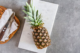 Fresh pineapple on a white marble platter on a stone surface