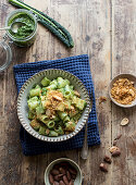 Bowl of palatable pasta paccheri with fresh kale pesto and ground peanuts