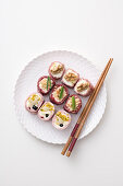 Sushi-style canapés with sausage, fruit and cheese