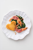 King prawns wrapped in bacon on spinach with a polenta heart