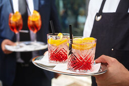 A waiter carrying cocktails on a tray (Campari Soda and Aperol Spritz)