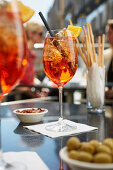 Aperol Spritz, olives, almonds and grissini in a restaurant