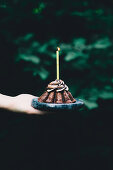 A hand holding a chocolate espresso cake with a birthday candle