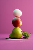 A pear, an apple and an egg stacked on top of each other with a bunch of thyme