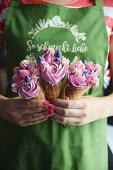A woman holding three ice cream cones