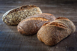 Three different loaves of seeded bread