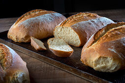 Three loaves of freshly baked white bread, one sliced