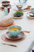Carrot soup in turquoise bowl and bread on set table