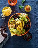 A bowl with beans, avocado, nachos, quinoa, cheese and chocolate (Mexico)
