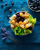 A bulgur bowl with goat's cheese filo pastry rolls, blueberries, lettuce and lavender