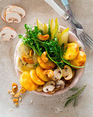 A bowl with polenta fritters, rocket, pears, mozzarella, mushrooms and cashew nuts