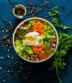 A bowl with rice, cucumber, tomato sauce and a poached egg