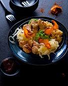 A bowl with Tandoori chicken, mushy peas, white cabbage and sweet potato crisps