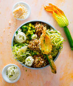 A bowl with stuffed courgette flowers, spelt, pistachio cream and Parmesan cheese