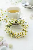 Camomile flowers with a teacup on a festive table