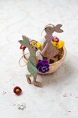 Wooden Easter bunnies with tufted pansies and daisies in a basket
