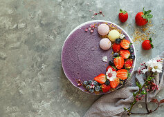 Vegan raw cashew cake with berries, coconut butter and coconut milk, and base made of almonds and dates