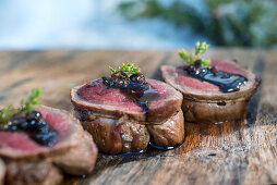 A winter barbecue: sliced elk roulade on a wooden board (Norway)