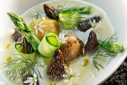 Natural cuisine: cream of potato soup with morel mushrooms, asparagus and edible flowers
