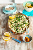Fish baked with couscous, spinach and curry creamy sauce