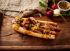 A hot dog with Nuremberger sausages, mustard and radishes