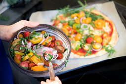 Preparing with pizza with tomatoe salad with truffle salami