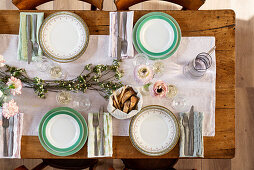 Laid wooden table with a white table runner and flower decorations